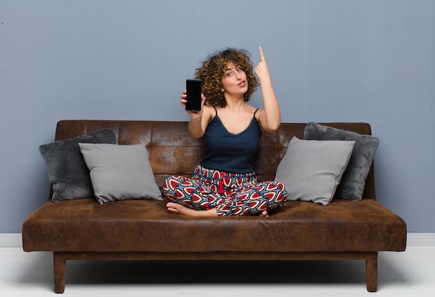 Junge hübsche frau zu hause, mit einem handy, pyjama auf einem sofa tragend