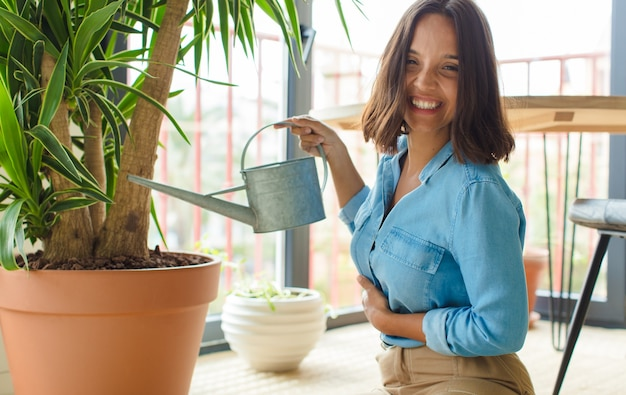 Junge hübsche frau zu hause mit pflanzen