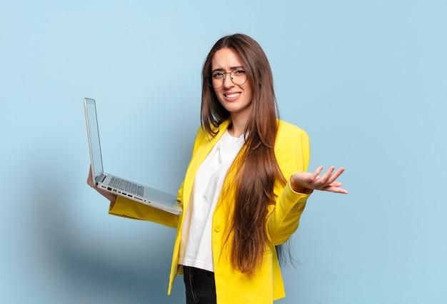 Junge hübsche freiberufliche frau, die einen laptop hält