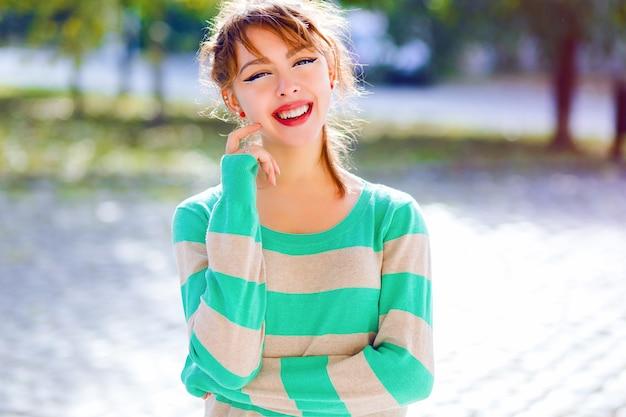 Junge hübsche fröhliche asiatische teenager-mädchen, die an einem schönen sommertag im stadtpark posieren, haben eine positive spielerische stimmung, lächeln und haben spaß, tragen lässigen gestreiften pullover. helles lebensstilporträt.