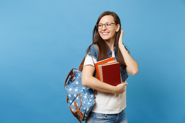 Junge hübsche fröhliche studentin in gläsern mit rucksack mit schulbüchern, die die korrektur der frisur berühren, die isoliert auf blauem hintergrund beiseite schaut. ausbildung am gymnasium.