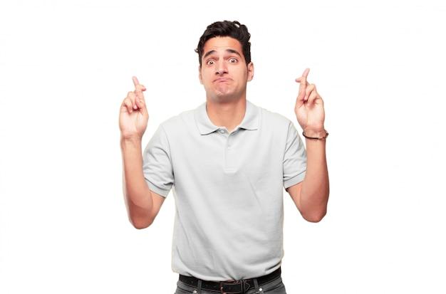 Junge hübsche gebräunte mannkreuzungsfinger, die für glück, mit einem hoffnungsvollen, eifrigen und aufgeregten expre wünschen
