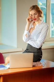 Junge hübsche geschäftsfrau am arbeitsplatz im büro. geschäftskonzept