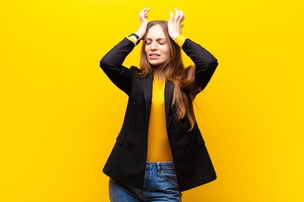 Junge hübsche geschäftsfrau, die betont und besorgt, niedergedrückt und mit kopfschmerzen frustriert sich fühlt und beide hände anhebt, um gegen orange voranzugehen