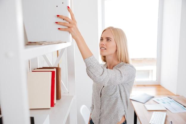 Junge hübsche geschäftsfrau, die ein buch aus einem regal nimmt, während sie im büro steht