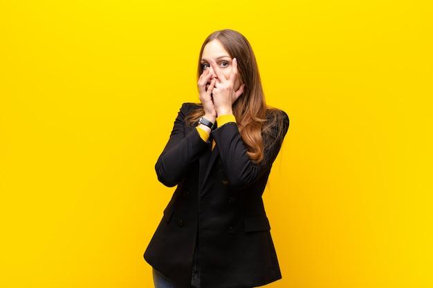 Junge hübsche geschäftsfrau, die erschrocken oder verlegen sich fühlt, mit den augen späht oder ausspioniert, die mit den händen gegen orange wand halb bedeckt sind