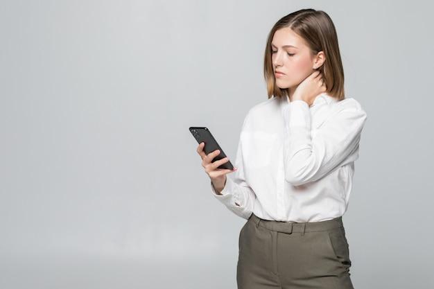Junge hübsche geschäftsfrau, die in telefonbildschirm hält, der nacken des schmerzes lokalisiert auf weißer wand hält