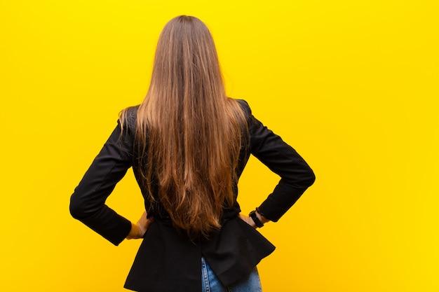 Junge hübsche geschäftsfrau, die verwirrt oder voll oder die zweifel und fragen, wundernd, mit den händen auf hüften, hintere ansicht gegen orange glaubt