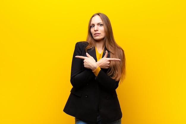 Junge hübsche geschäftsfrau, die verwirrt und verwirrt schaut, in entgegengesetzte richtungen mit zweifeln gegen orange unsicher und zeigt