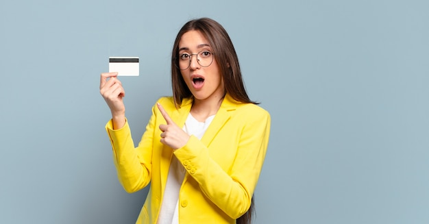 Junge hübsche geschäftsfrau mit einer kreditkarte