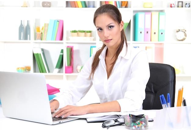 Junge hübsche geschäftsfrau mit notizbuch im büro