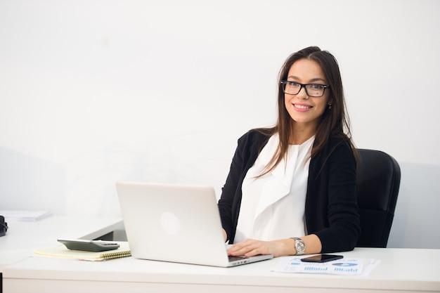 Junge hübsche geschäftsfrau mit notizbuchlaptop im büro