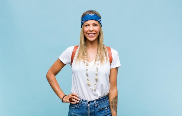 Junge hübsche hippie-frau, die glücklich mit einer hand auf hüfte und selbstbewusster, positiver, stolzer und freundlicher haltung lächelt