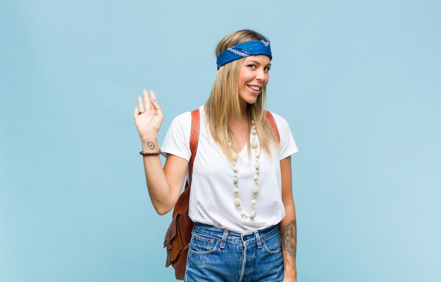 Junge hübsche hippie-frau, die glücklich und fröhlich lächelt, hand winkt, sie begrüßt und begrüßt oder sich verabschiedet