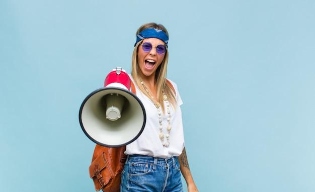 Junge hübsche hippiefrau mit einer ledertasche und einem megaphon