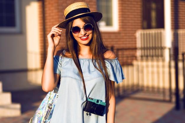 Junge hübsche hipster fröhliche frau, die auf der straße am sonnigen tag aufwirft, spaß allein hat, stilvolle weinlese-kleiderhut und sonnenbrille, reisekonzept, junger fotograf mit weinlesekamera.