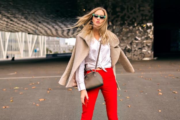 Junge hübsche hipsterfrau, die auf der straße nahe modernen geschäftszentren aufwirft, trendiges bürooutfit und kaschmirmantel trägt, kuss sendet und kühlen herbsttag genoss, getönte farben.