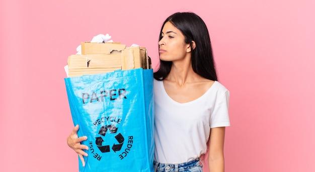 Junge hübsche hispanische frau auf der profilansicht, die nachdenkt, sich vorstellt oder träumt und eine papiertüte hält, um sie zu recyceln