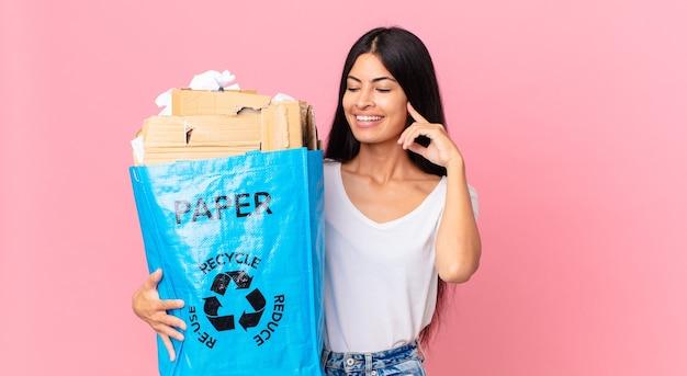 Junge hübsche hispanische frau, die glücklich lächelt und träumt oder zweifelt und eine papiertüte hält, um sie zu recyceln