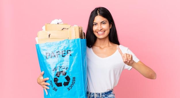 Junge hübsche hispanische frau, die lächelt und freundlich aussieht, die nummer eins zeigt und eine papiertüte zum recyceln hält