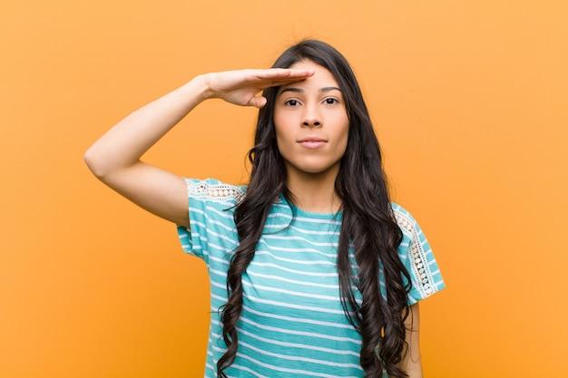 Junge hübsche hispanische frau, die mit einem militärischen gruß grüßt