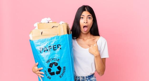 Junge hübsche hispanische frau, die schockiert und überrascht mit weit geöffnetem mund aussieht, auf sich selbst zeigt und eine papiertüte zum recyceln hält