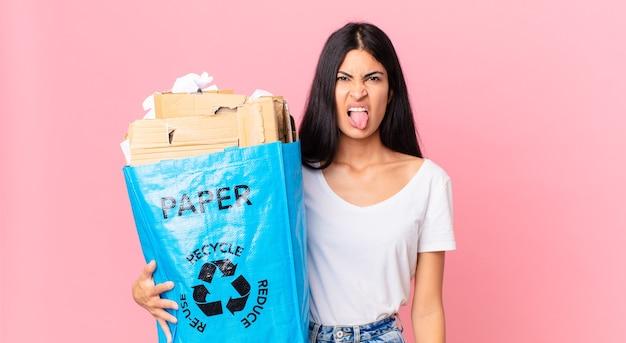 Junge hübsche hispanische frau, die sich angewidert und irritiert fühlt und die zunge herausstreckt und eine papiertüte zum recyceln hält
