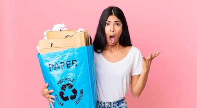 Junge hübsche hispanische frau, die sich extrem schockiert und überrascht fühlt und eine papiertüte zum recyceln hält