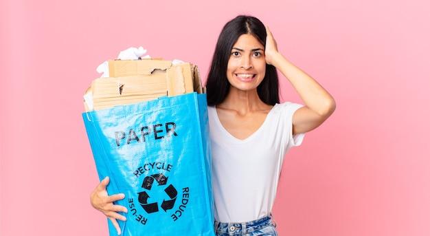 Junge hübsche hispanische frau, die sich gestresst, ängstlich oder ängstlich fühlt, mit den händen auf dem kopf und einer papiertüte zum recycling hält