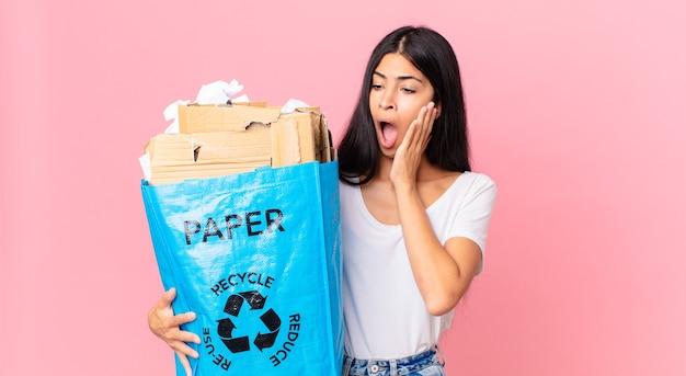 Junge hübsche hispanische frau, die sich glücklich, aufgeregt und überrascht fühlt und eine papiertüte zum recyceln hält