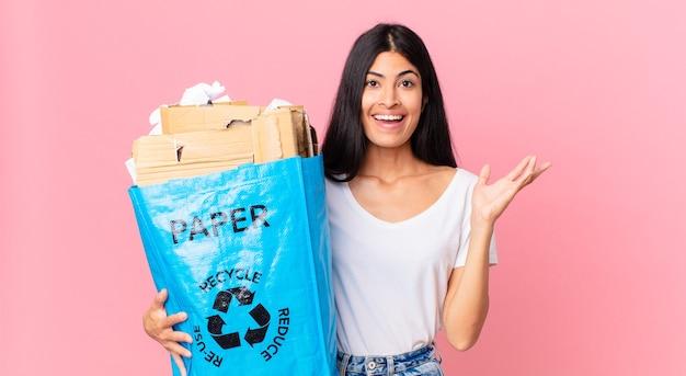 Junge hübsche hispanische frau, die sich glücklich fühlt, überrascht, eine lösung oder idee zu erkennen und eine papiertüte zum recycling zu halten