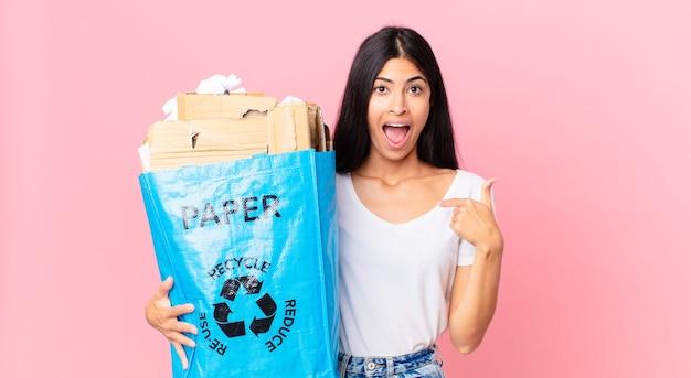 Junge hübsche hispanische frau, die sich glücklich fühlt und auf sich selbst zeigt, aufgeregt und hält eine papiertüte zum recyceln