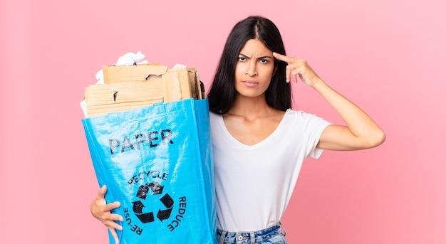 Junge hübsche hispanische frau, die sich verwirrt und verwirrt fühlt, zeigt, dass sie verrückt sind und eine papiertüte zum recycling hält
