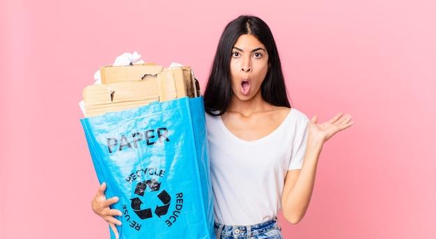 Junge hübsche hispanische frau, die überrascht und schockiert aussieht, mit heruntergefallenem kiefer, die einen gegenstand hält und eine papiertüte zum recyceln hält