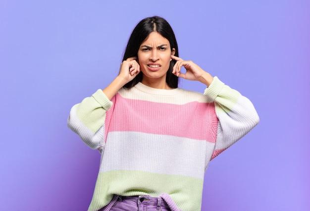 Junge hübsche hispanische frau, die wütend, gestresst und verärgert aussieht und beide ohren zu einem ohrenbetäubenden geräusch, ton oder lauter musik bedeckt