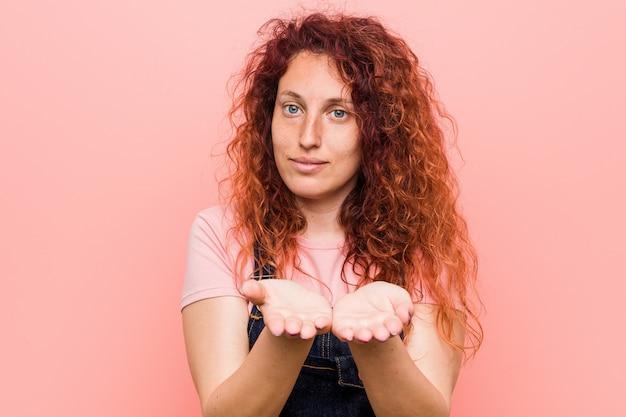 Junge hübsche ingwer-rothaarigefrau, die einen jeanslatzhose hält etwas mit den palmen, anbietend zur kamera trägt.
