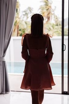 Junge hübsche kaukasische frau allein im sommer süßes kleid im urlaub an luxusvilla