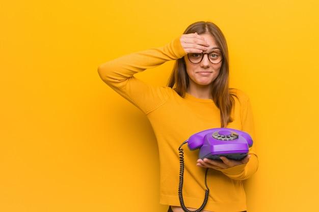 Junge hübsche kaukasische frau besorgt und überwältigt. sie hält ein altes telefon in der hand.