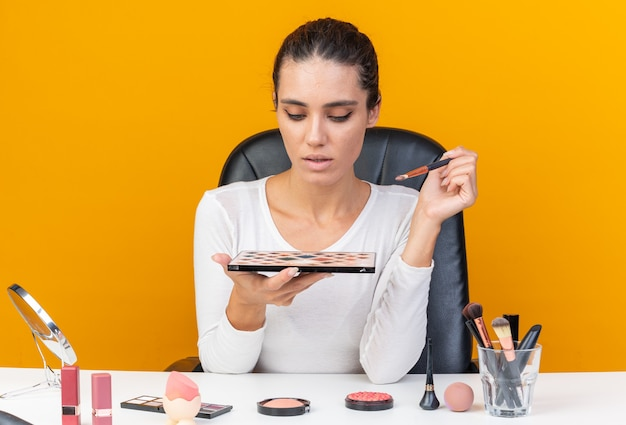 Junge hübsche kaukasische frau, die am tisch mit make-up-tools sitzt und make-up-pinsel und lidschatten-palette hält