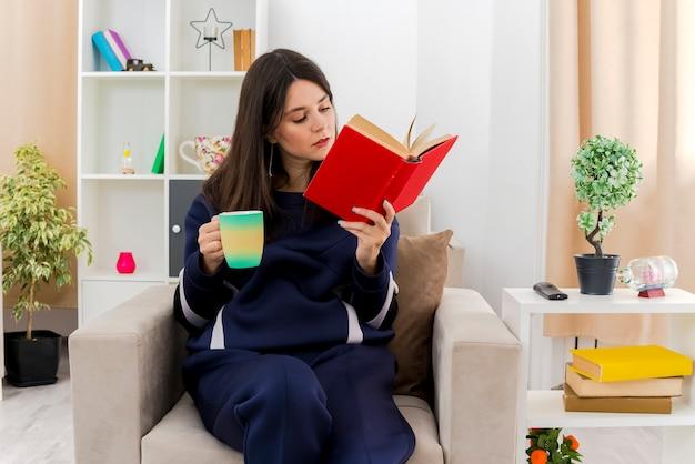 Junge hübsche kaukasische frau, die auf sessel im entworfenen wohnzimmer hält tasse und lesebuch sitzt