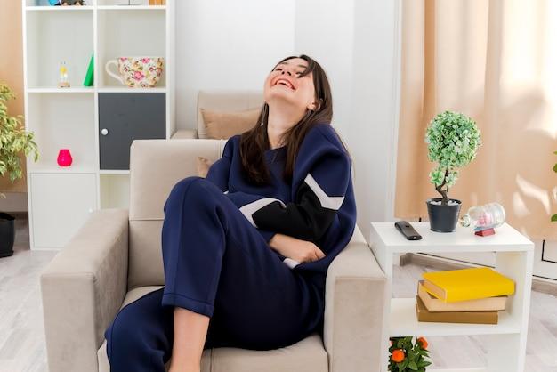 Junge hübsche kaukasische frau, die auf sessel im entworfenen wohnzimmer sitzt, die hände gekreuzt hält und mit geschlossenen augen lacht