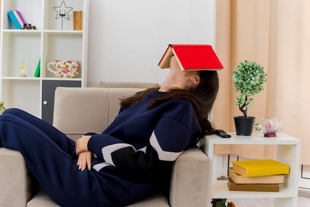 Junge hübsche kaukasische frau, die auf sessel im gestalteten wohnzimmer hält buch hält