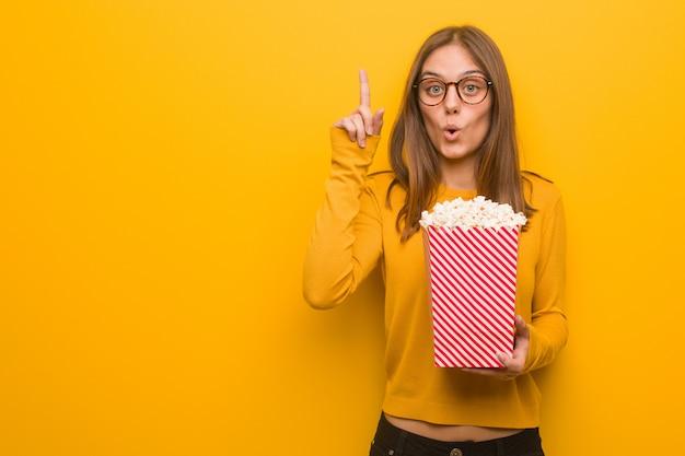 Junge hübsche kaukasische frau, die eine großartige idee, konzept der kreativität hat. sie isst popcorn.