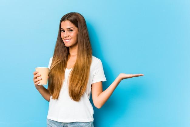 Junge hübsche kaukasische frau, die einen kaffee zum mitnehmen hält, der einen kopienraum auf einer handfläche zeigt und eine andere hand auf taille hält.