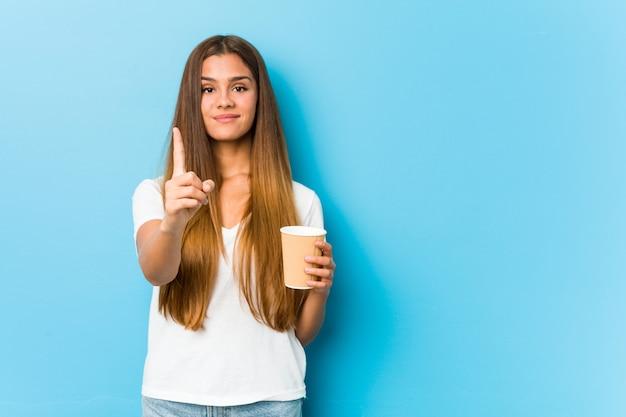 Junge hübsche kaukasische frau, die einen kaffee zum mitnehmen hält, der nummer eins mit finger zeigt.