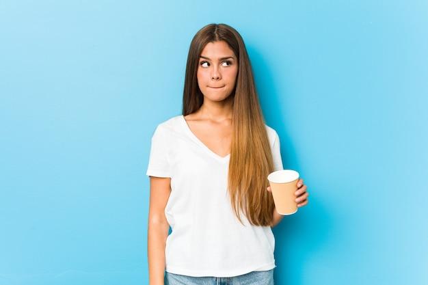 Junge hübsche kaukasische frau, die einen kaffee zum mitnehmen verwirrt hält, fühlt sich zweifelhaft und unsicher.