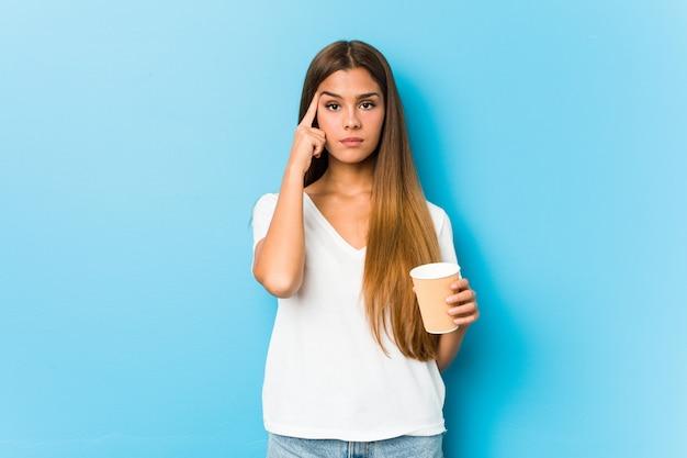 Junge hübsche kaukasische frau, die einen kaffee zum mitnehmen zeigt, der tempel mit dem finger zeigt und denkt, sich auf eine aufgabe konzentriert.