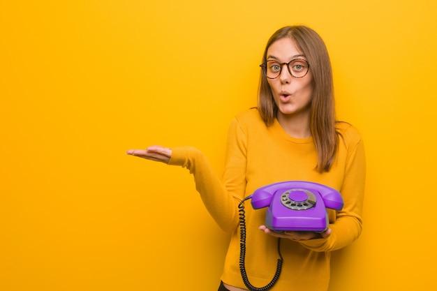 Junge hübsche kaukasische frau, die etwas auf palmenhand hält. sie hält ein altes telefon in der hand.