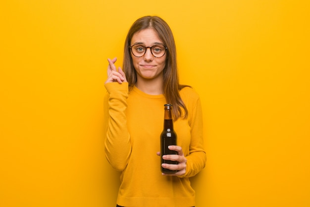 Junge hübsche kaukasische frau, die finger für glück kreuzt. sie hält ein bier.