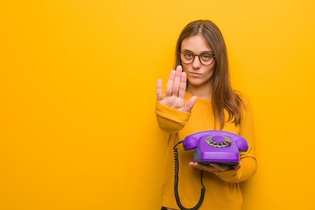Junge hübsche kaukasische frau, die hand in front einsetzt. sie hält ein altes telefon in der hand.